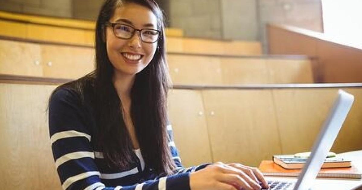 smiling-student-using-laptop-at